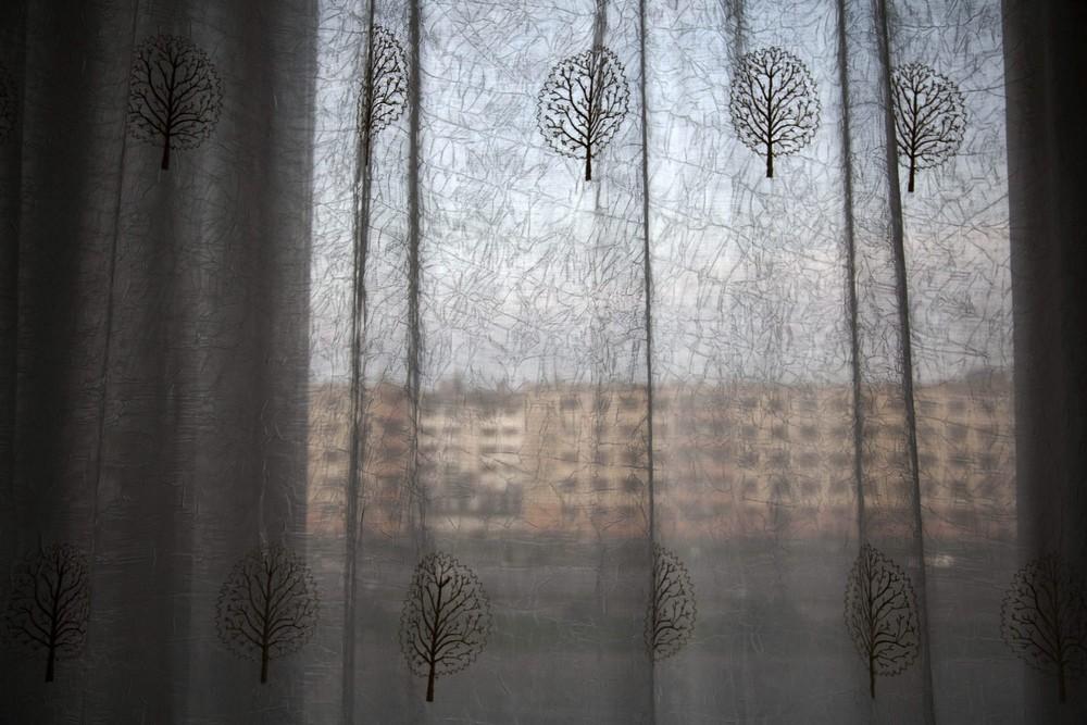 10. Многоквартирный дом виднеется за окном гостиницы на главной улице Хамхына. (Photo by David Gutte