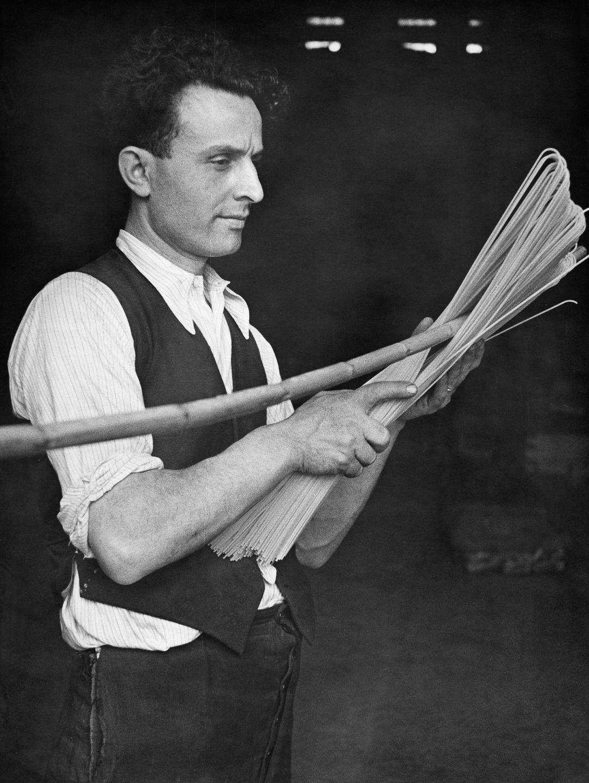 Работник итальянской фабрики сгибает высушенные спагетти при помощи палки, 1932 год.
