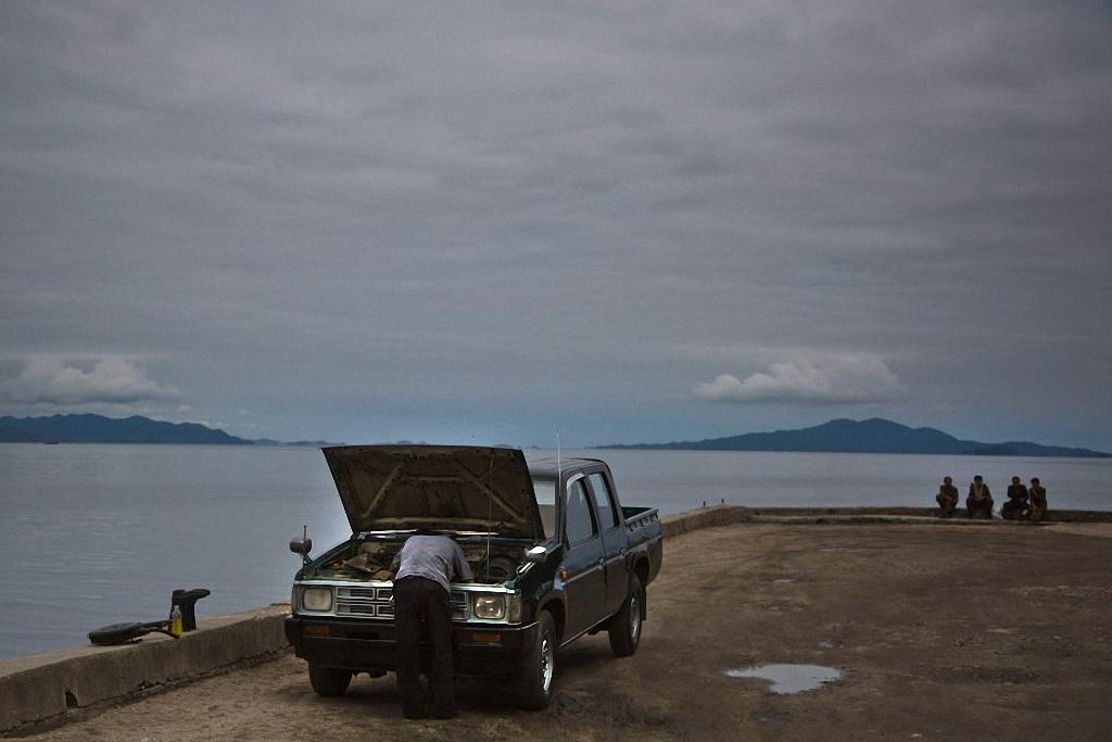3. Мужчина проверяет состояние двигателя автомобиля на берегу моря в городе Вонсан. (Фото: AP Photo
