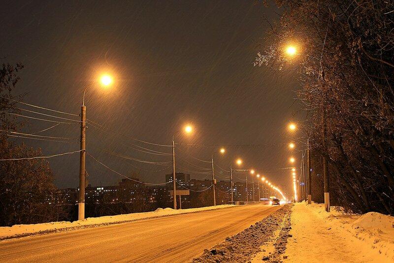 Треки падающих снежинок в виде черточек на огнях фонарей зимней ночью на старом мосту через Вятку
