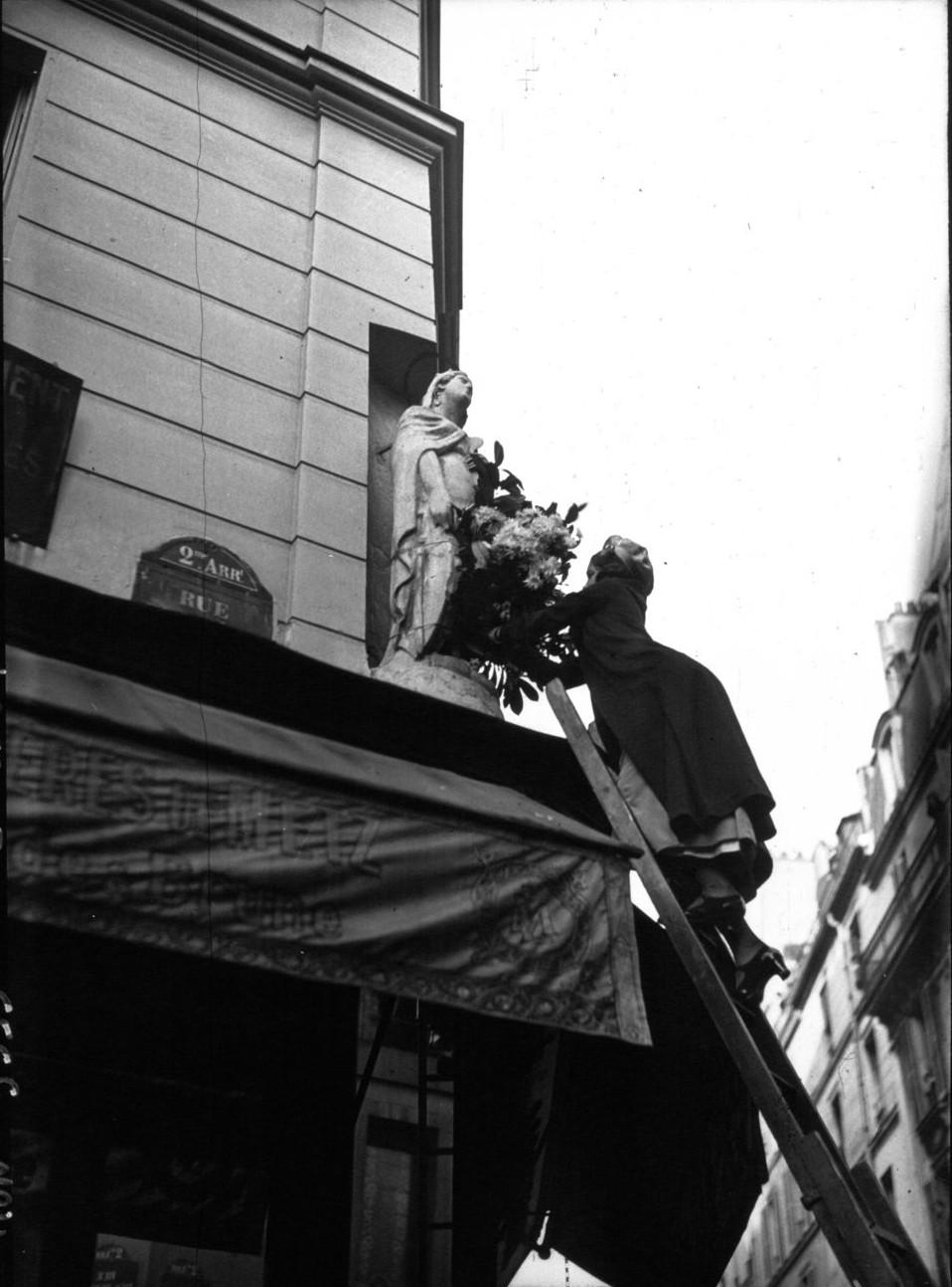 Продавщица цветов украшает статую Святой Екатерины на улице Клери