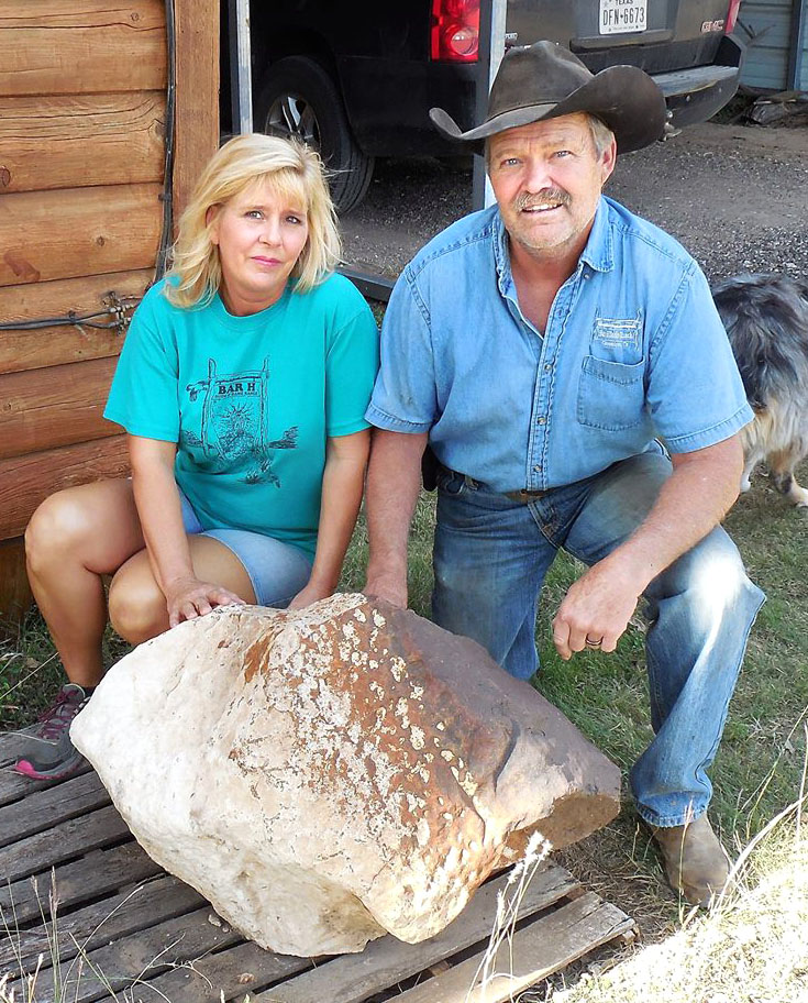 DeeDee and Frank Hommel pose with the 760 pound (345 kilogram) Clarendon (c) meteorite discovered on their land. The stony meteorite may be the second largest single chondrite ever found in the United States. It displays dark fusion crust on the topside; the bottom side, which faced down in the soil, is covered with caliche (ka-LEE-chee), a cement-like mineral deposit of calcium carbonate.
