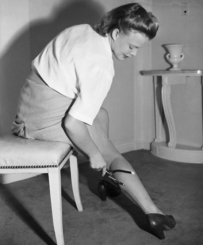 13. 1942 год. Девушка создает рисунок чулка посредством оригинального приспособления из элементов от