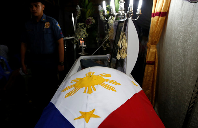 A policeman stands guard beside the flag-draped coffin of fellow officer Rancel Cruz, whom police in