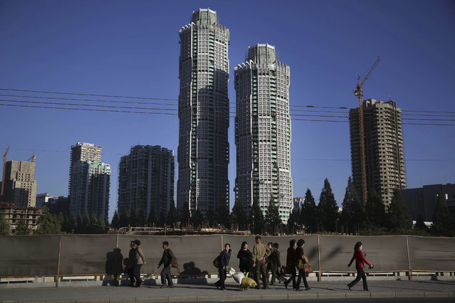 "North Korean men and women walk past buildings under construction on ""Ryomyong Street"", Monday, Octo"