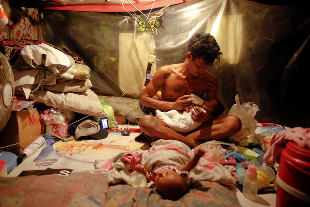 A man who lives with his family in a tent erected atop a tombstone, feeds his two-month old twins at