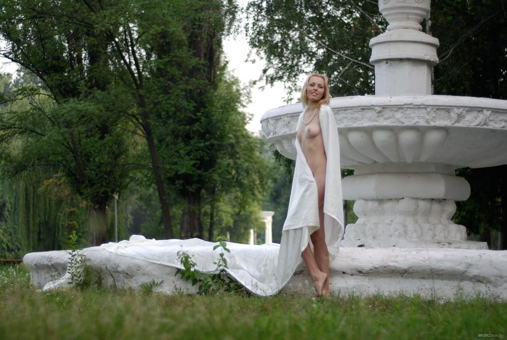 Белокурая Alina Porter возле фонтана