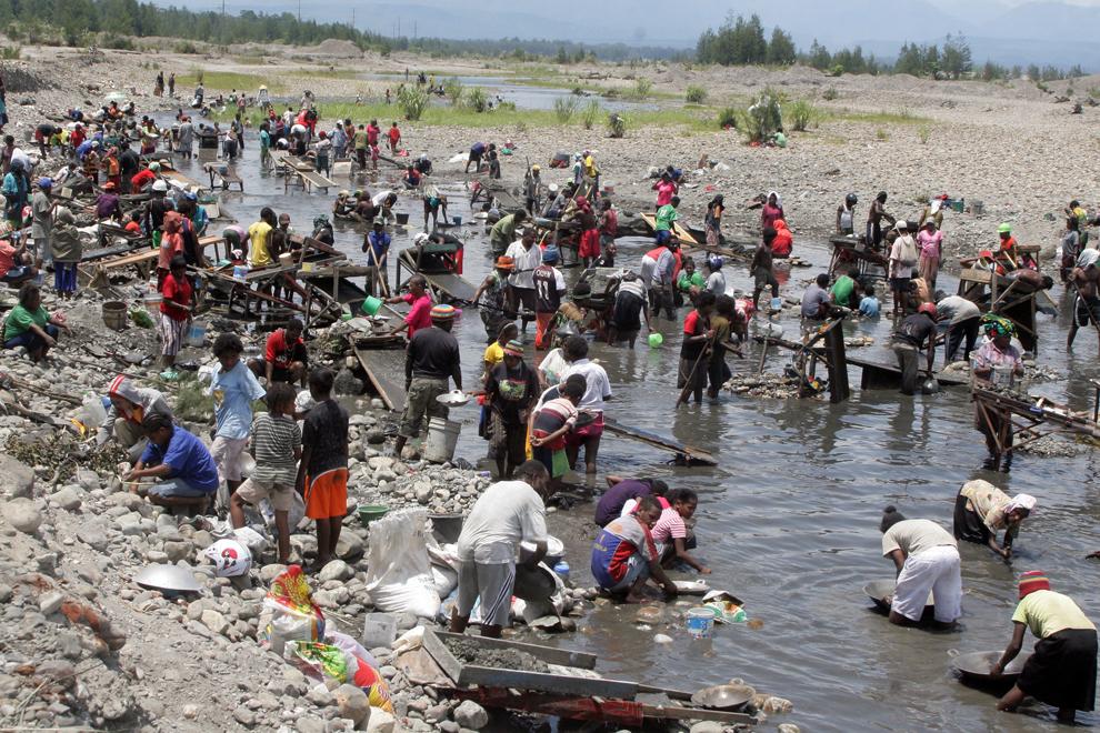 10. Жители папуасской деревни намывают золото в воде, которая выливается из протечки в трубе завода
