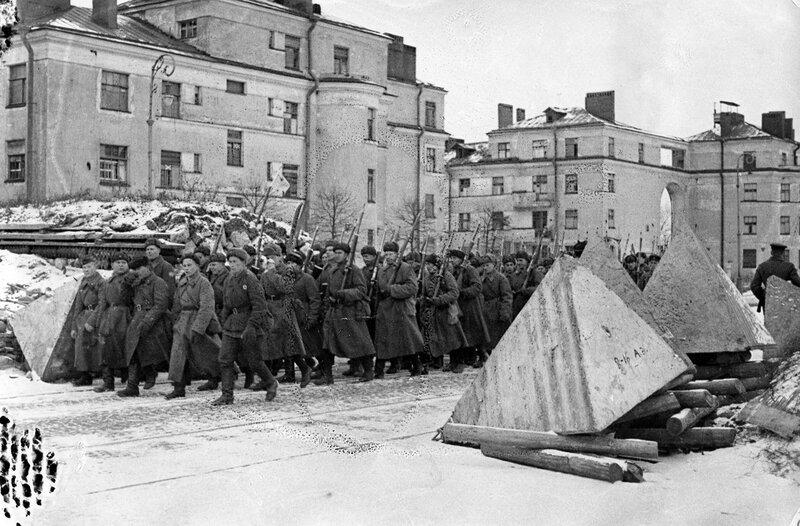 Красноармейцы проходят мимо надолб на проспекте Стачек
