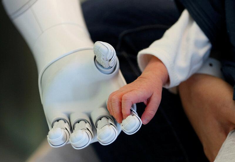 Гуманоидный робот Пеппер — новый «сотрудник» больницы AZ Damiaan в Остенде, Бельгия. В его задачи входит приветствовать посетителей и заботиться о пациентах. На фото он держит за руку новорожденного младенца, 16 июня 2016 года. (Francois Lenoir / Reuters)
