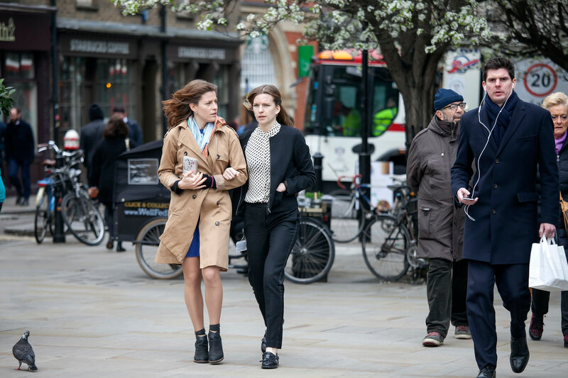 Two young girls with long hair are walking in the Spitalfield market area against a backdrop of flowering trees