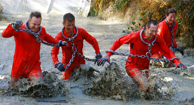 Competitors in costumes cross a water obstacle during the Wildsau Dirt Run (Wild Boar Dirt Run) obst