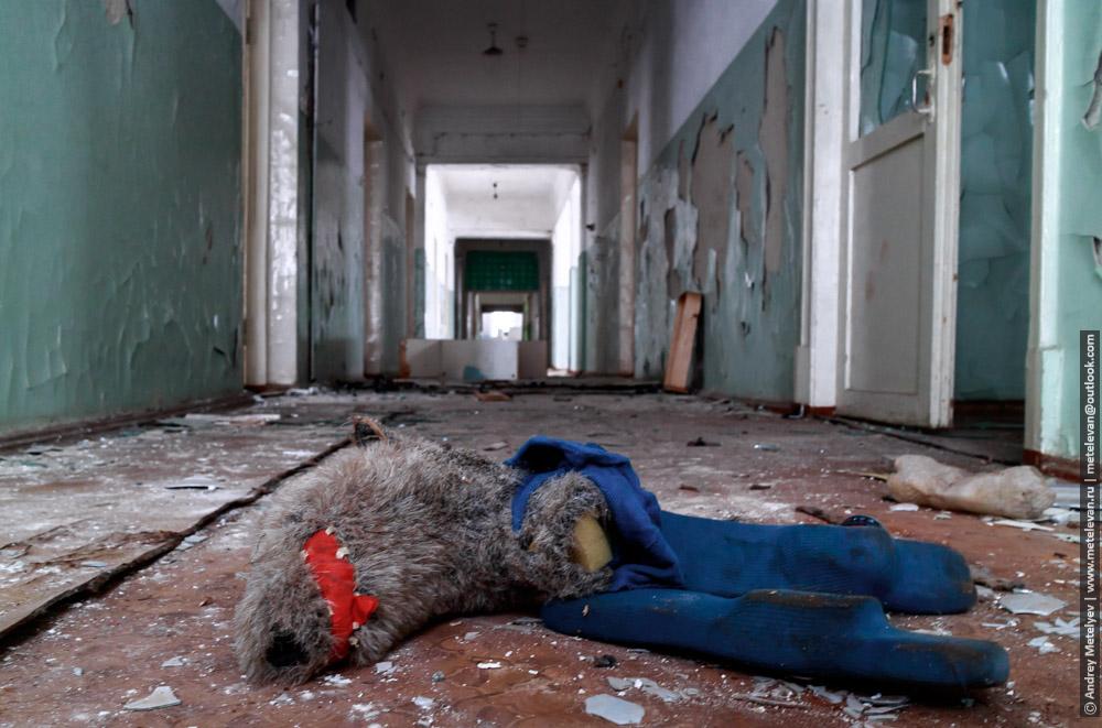 игрушка на фотоне стен заброшенного здания