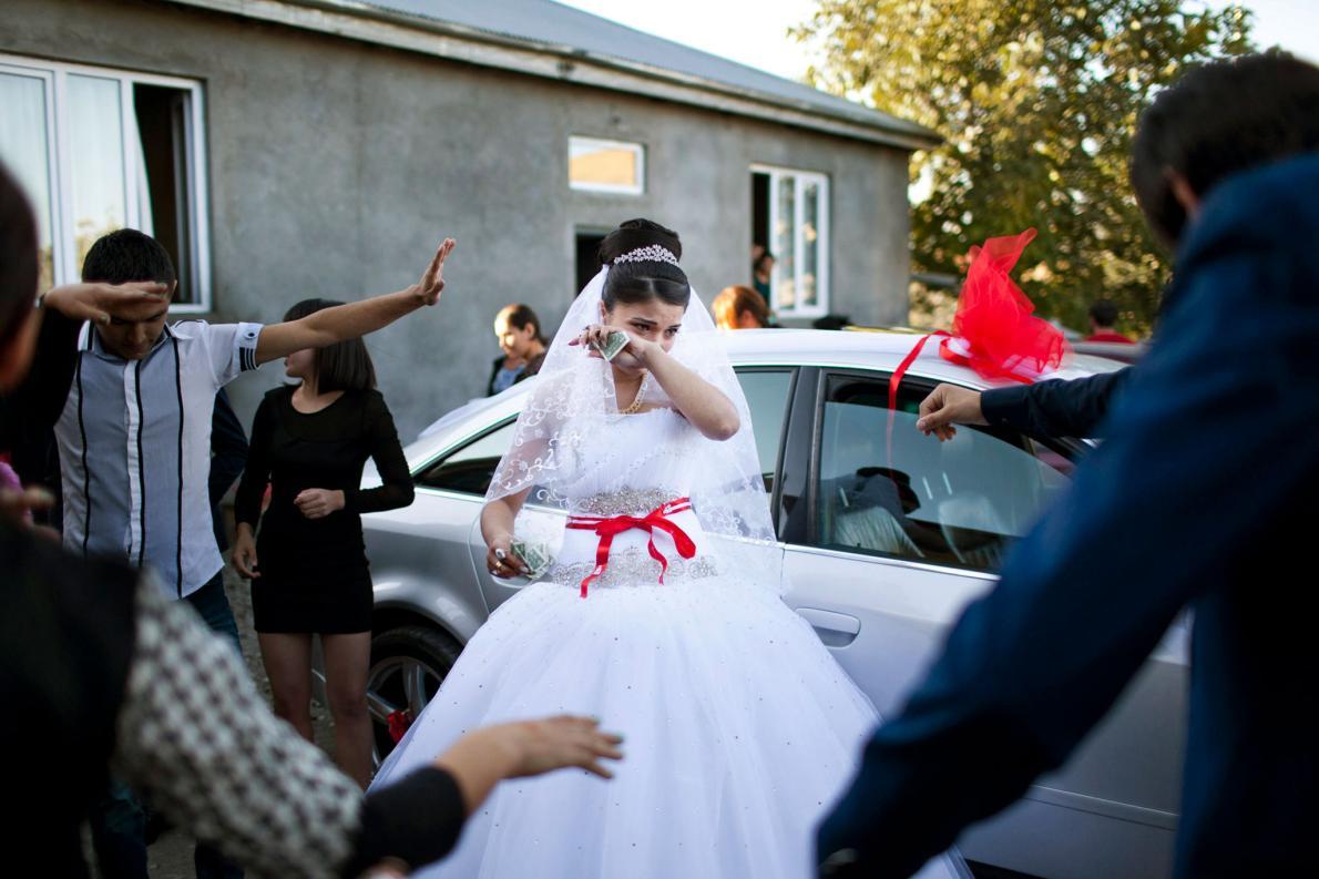 Друзья и родственники танцуют вокруг невесты, а она получает подарки в виде денег и плачет. Через го