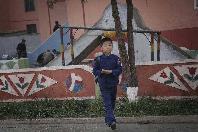 A North Korean boy in his school uniform walks past a playground in a residential area on Saturday,
