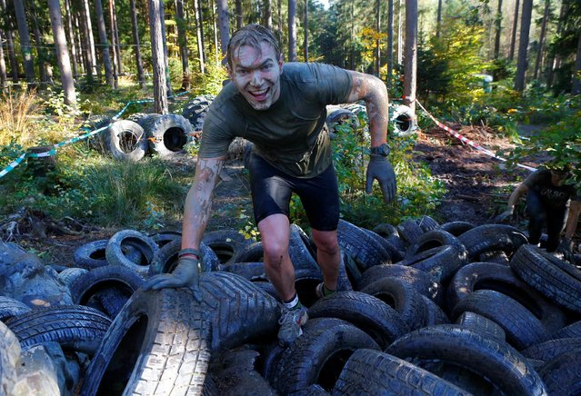 A competitor climbs over tyres during the Wildsau Dirt Run (Wild Boar Dirt Run) obstacle course fun