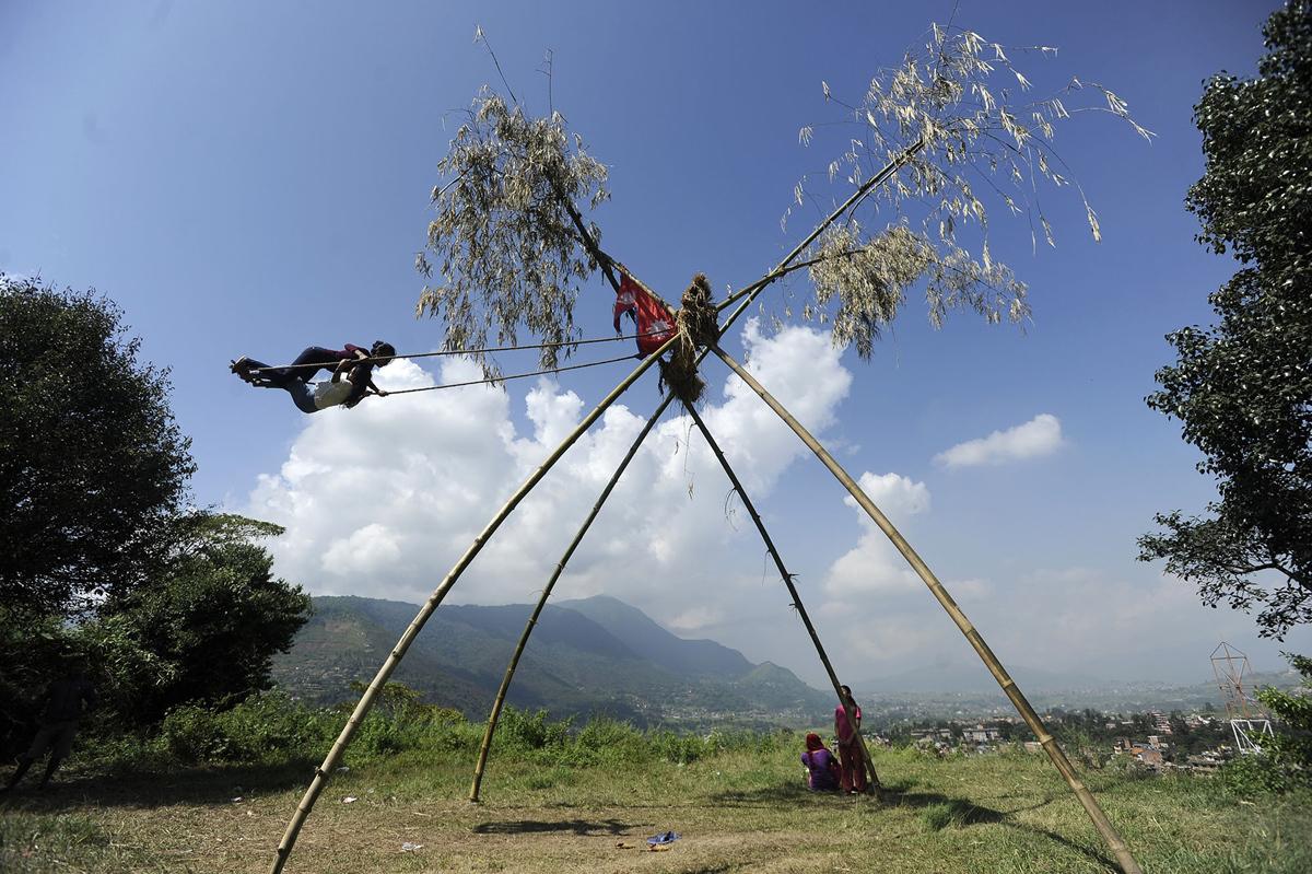 16. Непальские дети играют на качелях, называемых «пинг», во время национального фестиваля Дашайн в