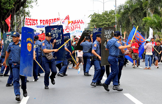 Various activist and Indigenous People's (IP) groups run towards anti-riot policemen during a p