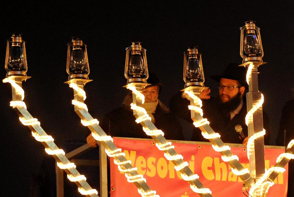 11. Раввин Шалом Бер Стэмблер (справа) зажигает свечи на большой меноре в центре Варшавы во время ев