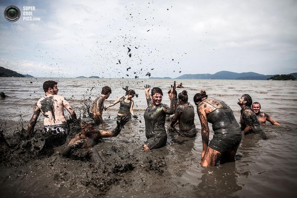 Гуляки плещутся в грязи. (Victor MORIYAMA/AFP/Getty Images)