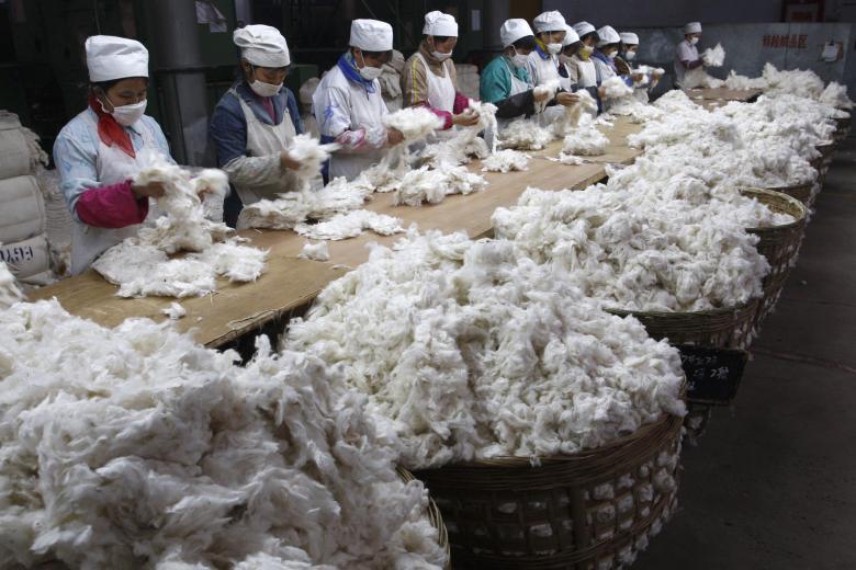 Работница раскрашивает копилки на фабрике по производству керамических изделий в провинции Фуцзянь.