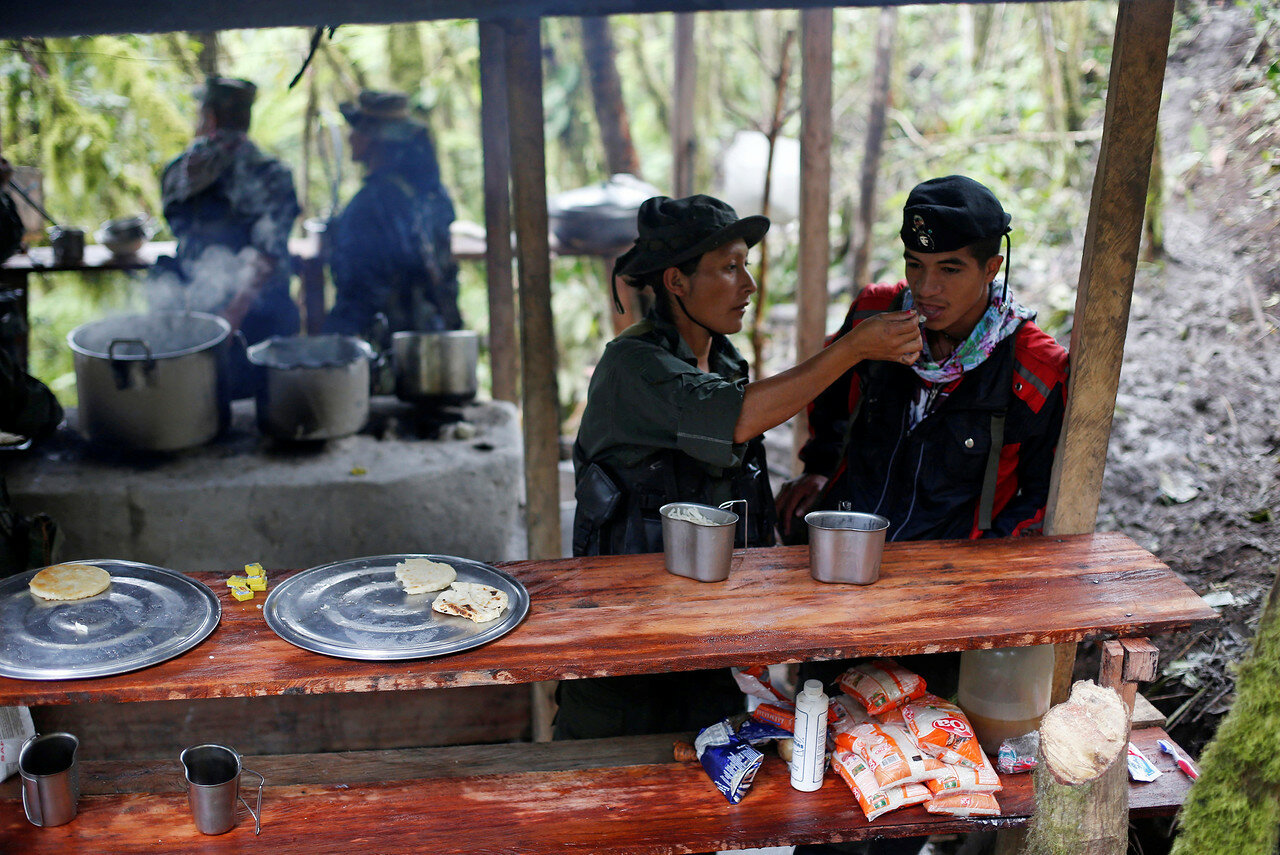 Yuli and Eduar of the 51st Front of the Revolutionary Armed Forces of Colombia (FARC) eat at a camp in Cordillera Oriental