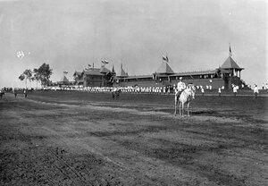 Император Николай II перед строем участников скачек; на заднем плане трибуны ипподрома