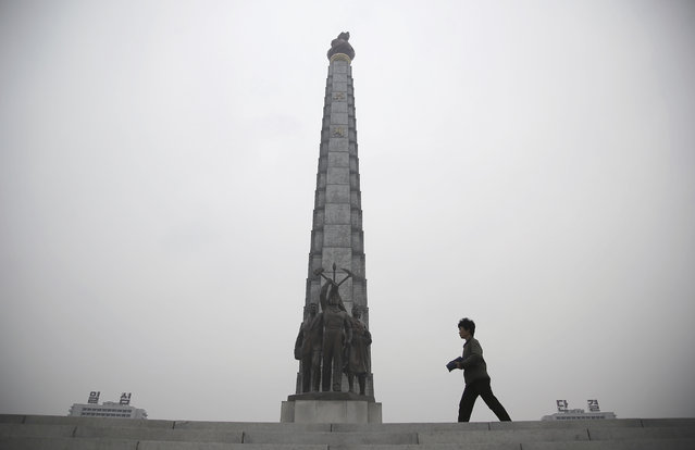 A North Korean woman is silhouetted as she walks past the Juche Tower and residential buildings on e