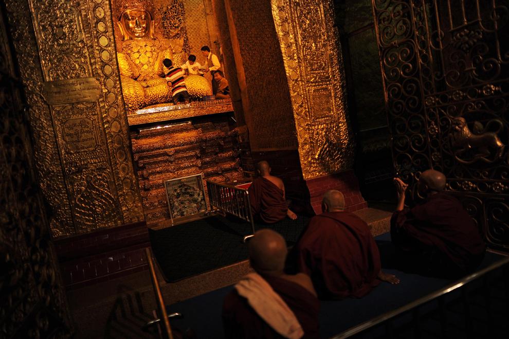 30. Буддийские монахи молятся в то время, как прихожане накладывают сусальное золото на статую сидящ
