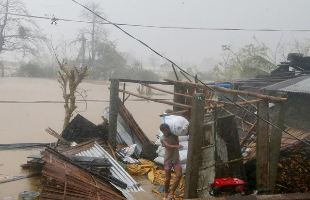 A resident carries a sack of rice after Super Typhoon Haima destroyed his home and caused flooding a