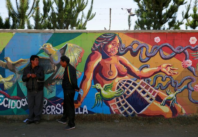 Men talk in front of graffiti in El Alto, Bolivia October 5, 2016. (Photo by David Mercado/Reuters)