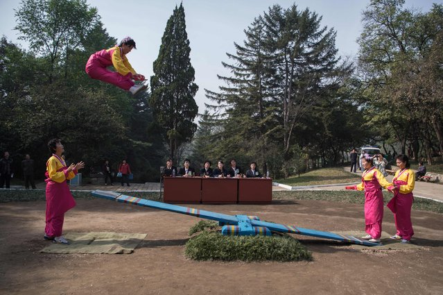 In a photo taken on October 15, 2016 competitors take part in a see-saw event during the 13th People