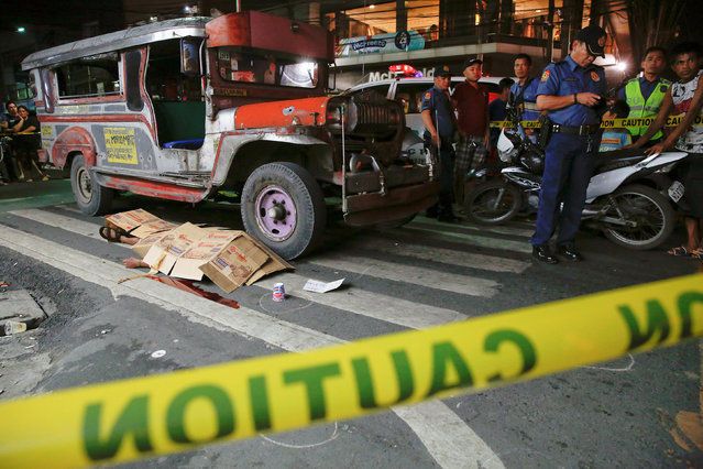 The body of a man killed by unknown gunmen is covered in Manila, Philippines early October 18, 2016.