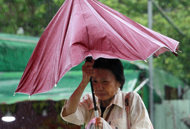 A woman struggles with her umbrella against powerful gusts of wind generated by typhoon Megi across
