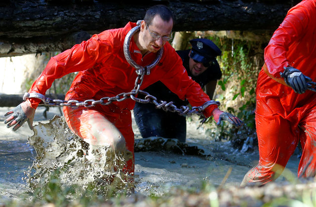 Competitors in costume cross a water obstacle during the Wildsau Dirt Run (Wild Boar Dirt Run) obsta