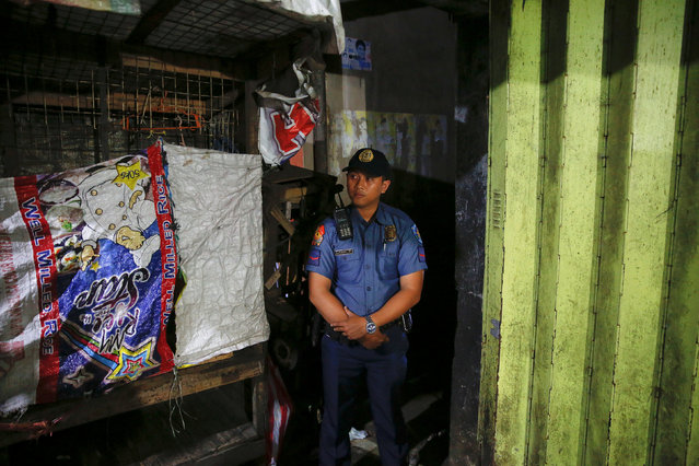 A policeman secures the entrance to the alley where a man was killed during a police drugs buy-bust