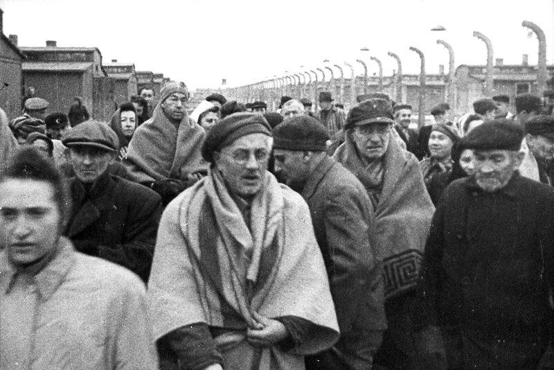 Освобожденные заключенные идут вдоль бараков