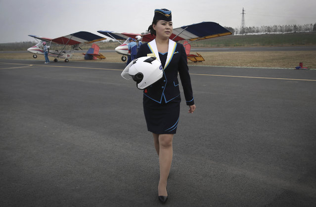 A staff member of the Mirim Air Club carries a helmet as she walks across the tarmac at the Mirim Ai