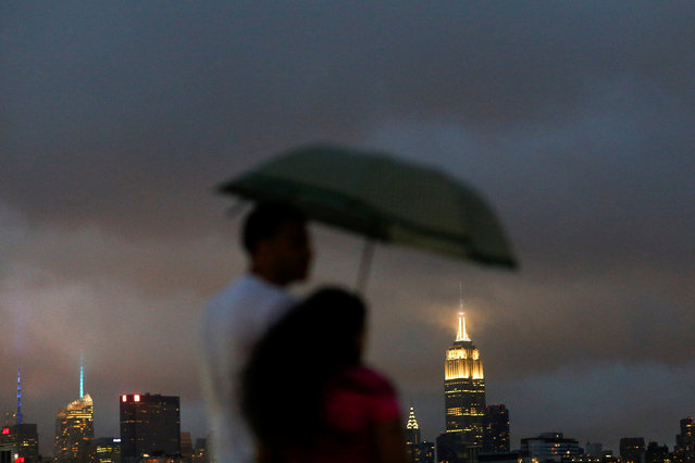 People cover from rain as a low level cloud formation hovers over New York's Empire State Build