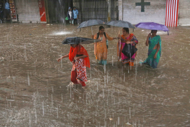 Indian women hold umbrellas and wade through a waterlogged street in the rain in Hyderabad, India, F