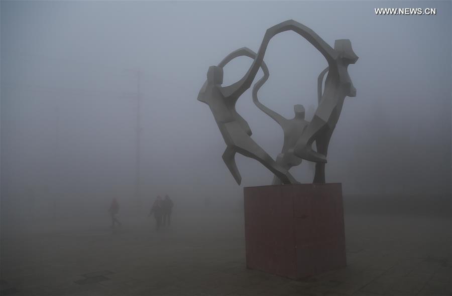 Пешеходы пробираются сквозь густой смог в городе Ляньюньган, провинция Цзянсу.