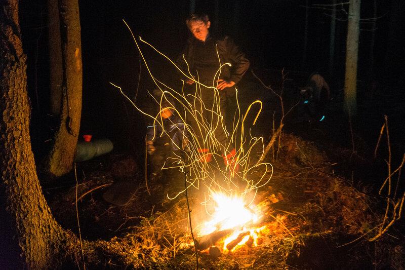 папа и ребенок у костра с искрами зимой в лесу