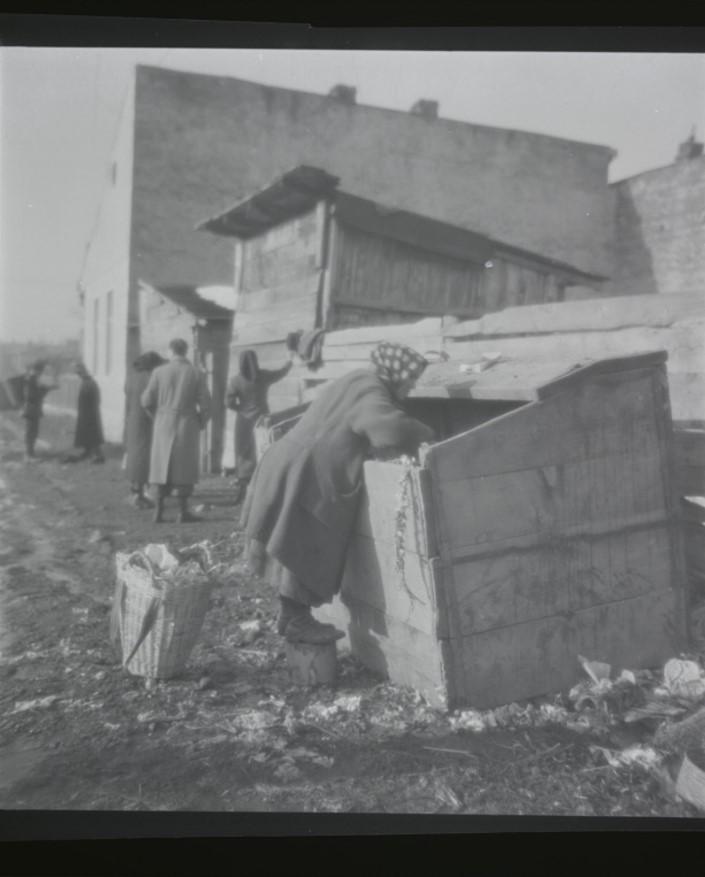 Женщина роется в мусоре