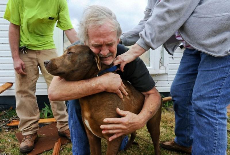 39. Грег Кук обнимает свою потерявшуюся собаку после того, как та нашлась. Алабама, после торнадо в