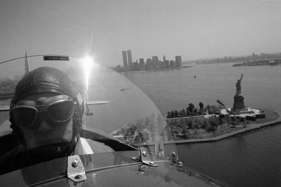 35. Капитан Бак Гилберт в кабине биплана 1929 года постройки над бухтой Нью-Йорка, 4 июня 1976 года.