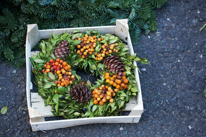 A natural twig wreath is decorated with pine cones, red berries, gold shells and a raffia bow.