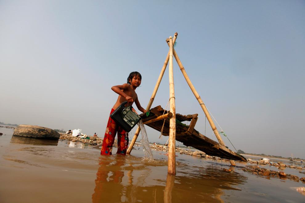 9. Девочка намывает золото в реке Иравади, штат Качин, Мьянма, 24 февраля 2012. В день она зарабатыв
