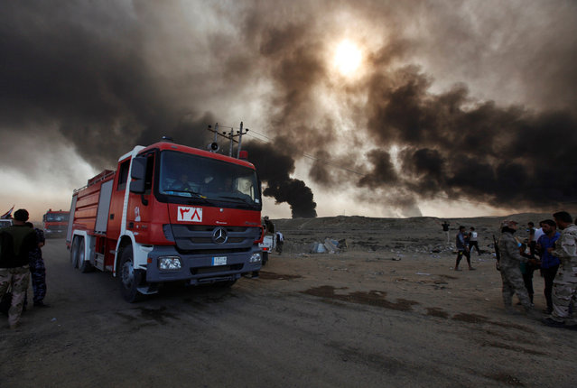 Fire trucks are seen in Qayyara, Iraq, October 22, 2016. The fumes in the background are from oil we