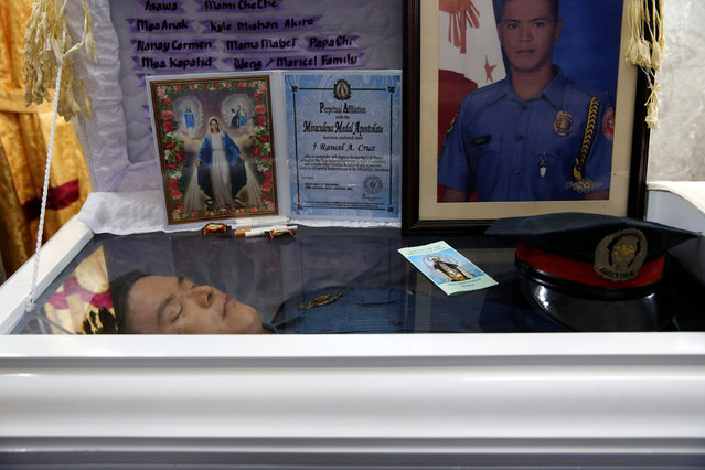 The body of policeman Rancel Cruz, whom police investigators said was shot dead by a drug addict, li