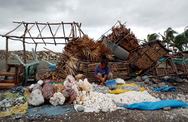A woman sorts decorative rocks outside her shop toppled during Typhoon Haima, in Pasuiquin, Ilocos N
